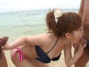 Young bikini babe, Rino Kirishima sucks two dicks on the beach