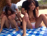 Two beautiful young Asian babes have fun on the beach