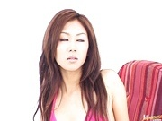 Really hot babe Rimu Himeno posiung in front of a camera takes two cocks.